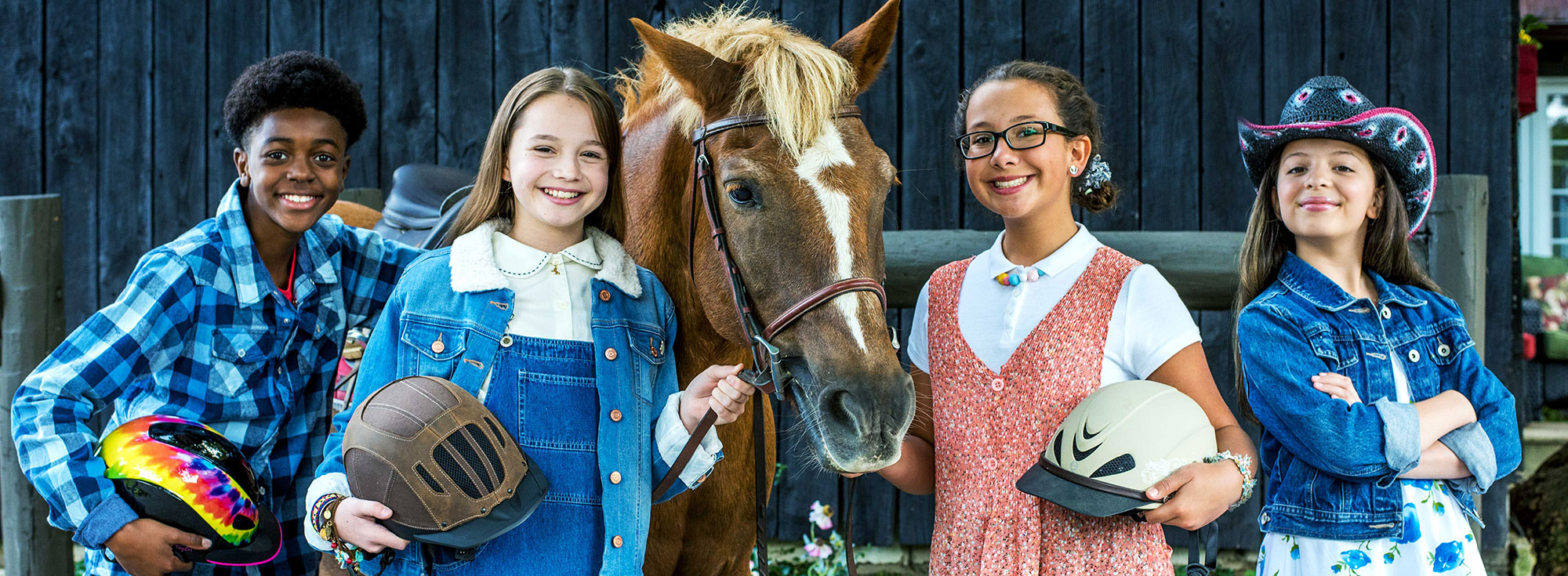 The young stars of Pony Sitters Club, posing with a horse