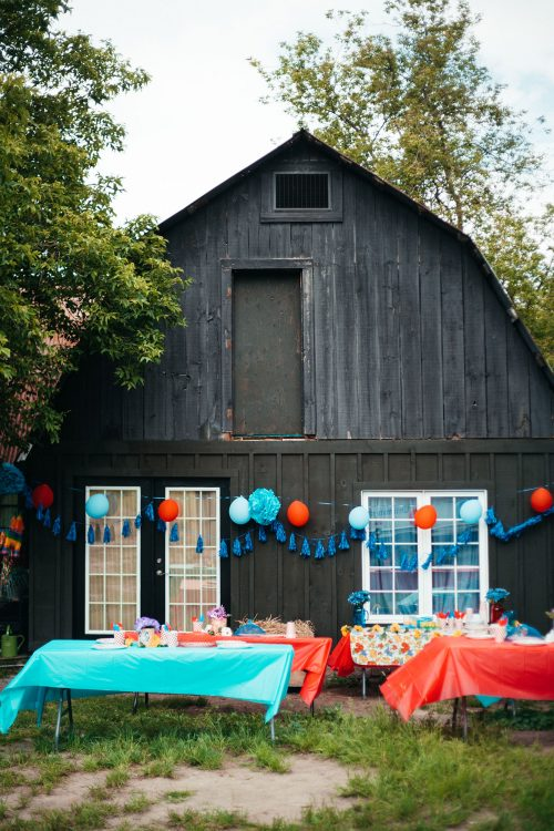 Party tables and balloons set up outside the ranch house