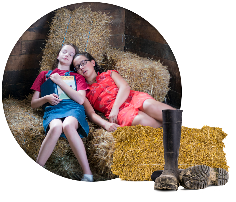 Two girls napping on bales of hay. Work boots in foreground.